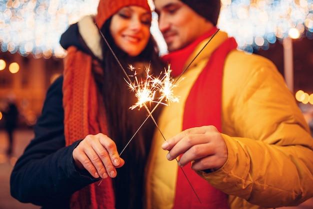 冬の夜、屋外の花火と愛のカップル。街でロマンチックな会議を持つ男女