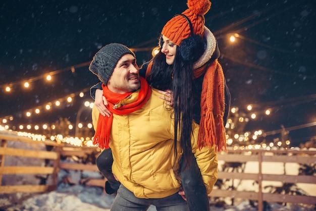 冬の夜、屋外で楽しんでいる遊び心のある愛のカップル。ライトと街の通りでロマンチックな会議を持っている男性と女性