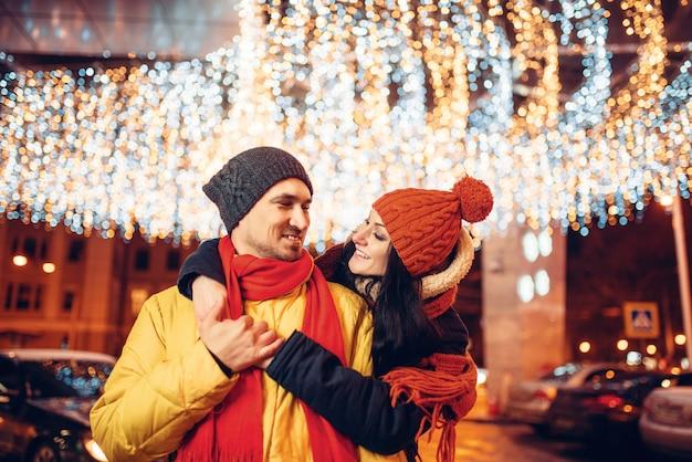 冬の夜、愛のカップルの笑顔を路上で抱擁