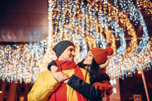 冬の夜、笑顔の愛のカップルが通りで抱擁します。ロマンチックな出会い、幸せな関係を持つ男女