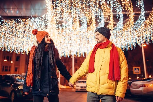 冬の夜、手をつないで歩く愛のカップルの笑顔。ロマンチックな会議、幸せな関係を持つ男女