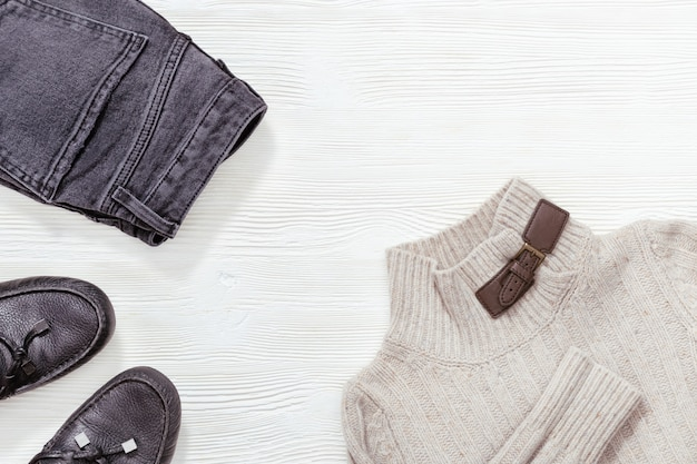 Winter, fall female clothing. black leather moccasins, dark jeans and light grey pullover on white wood background with copy space. flat lay.