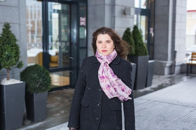 冬、ファッション、人々のコンセプト-若い女性の肖像画は屋外で散歩しています