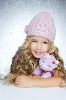 冬のファッションキャップ小さな女の子抱擁テディベア笑顔