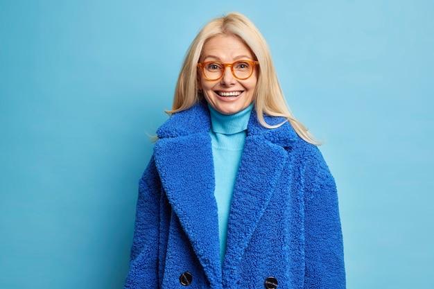 Concetto di moda invernale. donna bionda sorridente felice di mezza età indossa occhiali ottici e cappotto blu.