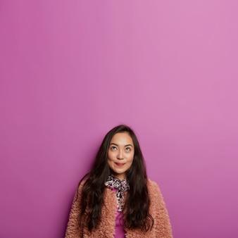겨울 패션, 사람, 아름다움, 생각 개념. 갈색 모피 코트에 잠겨있는 갈색 머리 아시아 여자는 위쪽으로 집중, 즐거운 것을 알아