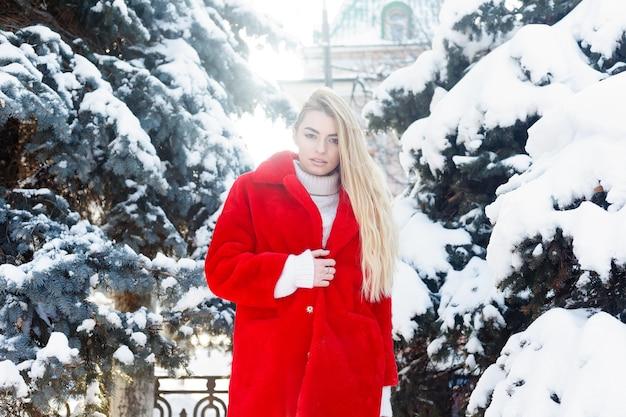 冬、ファッション、人々のコンセプト-ファッション美しい若い女性の肖像画は、赤い毛皮のコートのクローズアップ雪片の寒い冬を笑顔で街を歩き、霜の冬の日に新鮮な空気を吸います。日没