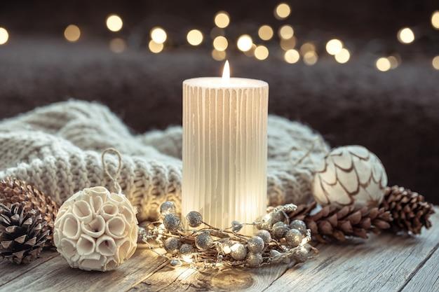 燃えるろうそくとボケ味のぼやけた背景の家の装飾の詳細と冬のお祭りの背景。