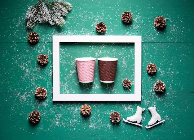 Зимние праздничные концепции рамки шишки еловые ветки бумажные стаканчики на зеленом деревянном фоне
