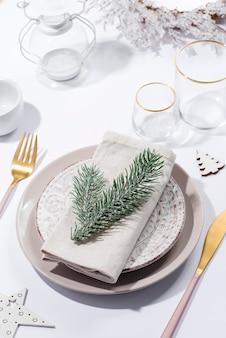 Сервировка праздничного стола зимой со столовыми приборами на столе. новогодняя посуда.