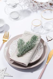 Winter festive table setting with cutlery on table. christmas tableware.