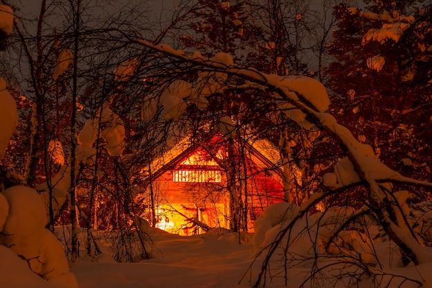겨울 핀란드. 울창한 숲과 많은 눈. 작은 목조 주택과 야간 조명