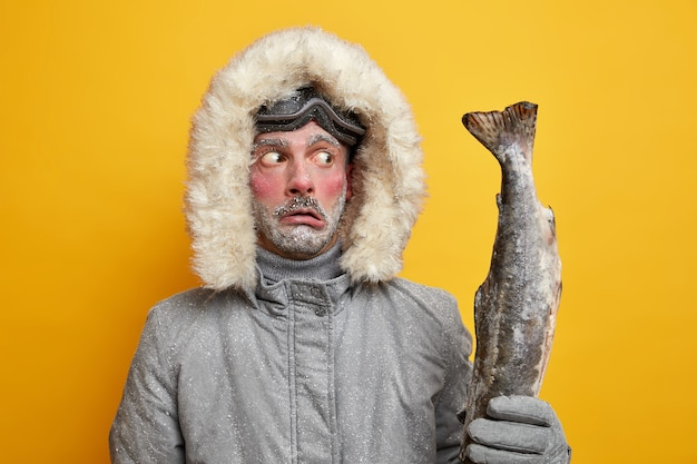 冬の釣りとスポーツのコンセプト。ショックを受けた凍った男は大きなトロフィーに唖然としている。釣った魚はアウターウェアを着ており、赤い顔は雪で覆われている。
