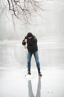 Winter fishing on the frozen lake with hand drill