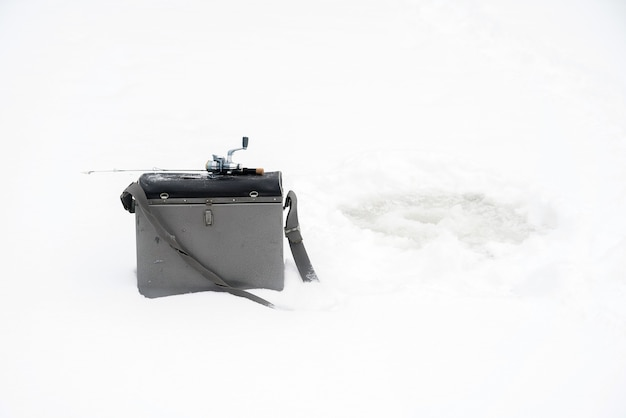 얼음에 겨울 낚시. 얼음 구멍에 미끼를 흔들고 있습니다.