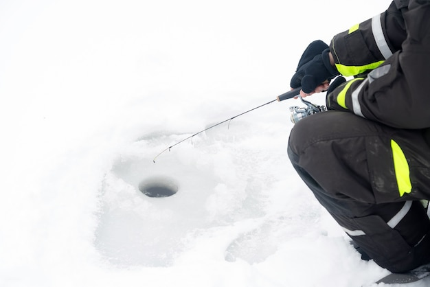 얼음에 겨울 낚시. 얼음 구멍에 미끼를 흔들고있는 남자.