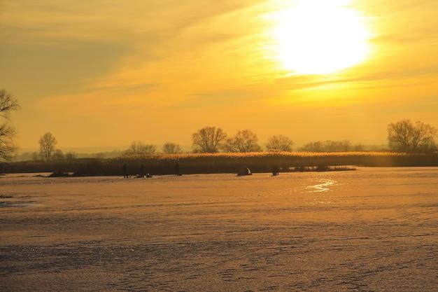 日没時の凍った川での冬の釣り