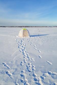 겨울 낚시 텐트는 호수 얼음 위에 설치됩니다.