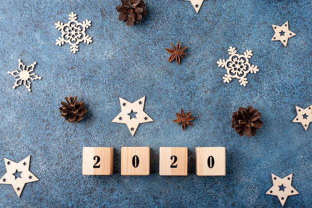 Winter flat lay with cinnamon, anise, cones, wooden snowflakes. happy new year 2020