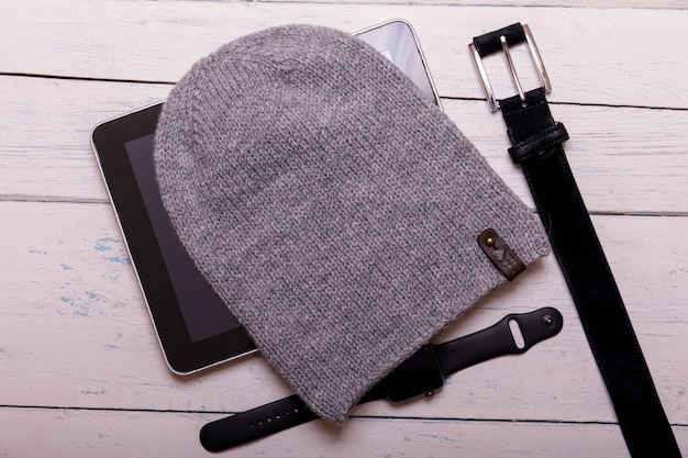 Winter flat lay with smartwatch, tablet, knitted hat and belt on white rustic wooden table. christmas and new year background.