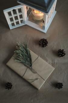 クラフト紙キャンドル松の小枝とコーンの上面図でクリスマスと新年の贈り物と冬のフラットレイ