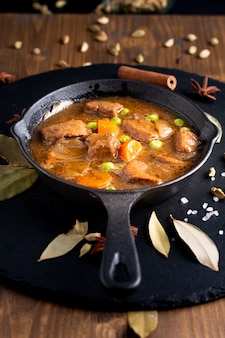 Winter food concept homemade organic stew beef or bourguignon in cast-iron skillet