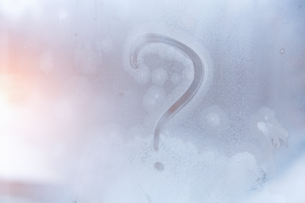 Winter frost, the inscription on the frozen glass - question mark.