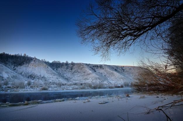 새벽 전에 겨울 서리가 내린 아침. 언덕이 많은 둑과 큰 빙원에서 흘러 내리는 강.