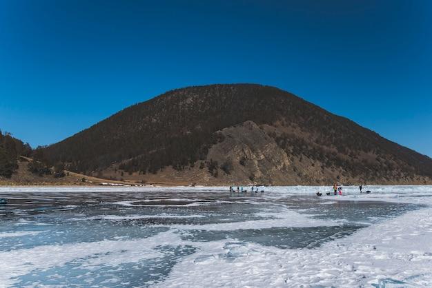 Зимнее замерзшее озеро днем на фоне горы