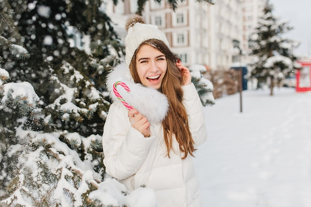 Tempo congelato di inverno della donna straordinaria divertente che si diverte con il lecca-lecca rosa sulla strada. giovane donna allegra che gode di nevicare in giacca calda, cappello lavorato a maglia, esprimendo positività. delizioso, dolce periodo invernale.