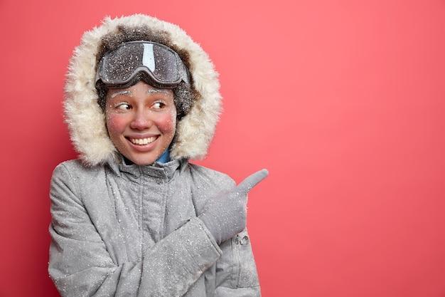 겨울 재미와 스키 개념. 겉옷을 입은 짙은 피부색의 아프리카 계 미국인 여성이 여백을 가리켜 12 월 시즌을 즐기는 휴양지 방향을 보여줍니다.