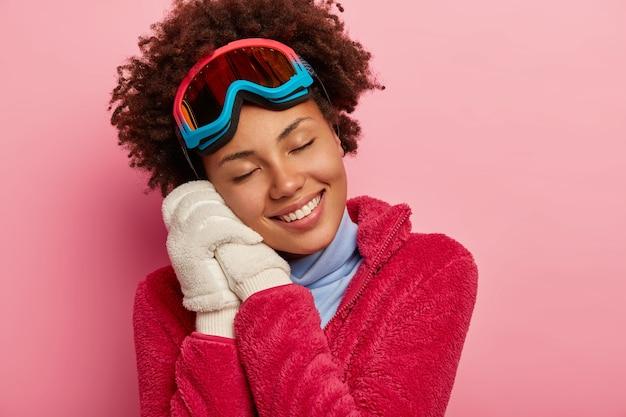 겨울 재미, 레크리에이션 및 라이프 스타일 개념. 어두운 피부를 가진 여자는 스노우 보드 안경을 쓰고 흰 장갑을 끼고 양손에 몸을 기울이고 휴가에서 즐거운 순간을 기억합니다.