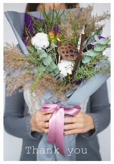 Зимняя девочка держит букет из хлопка, пишет спасибо.