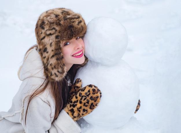 雪だるまを作る冬の女の子。雪の降る冬の散歩で雪だるまと遊ぶ幸せな女の子。冬の感情