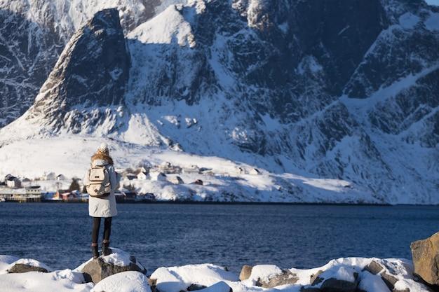 Winter. girl walks along the shore of the fjord. lofoten islands. norway