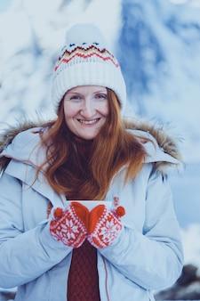 冬。ロフォーテン諸島のロルブの背景にカップを持つ少女。ノルウェー