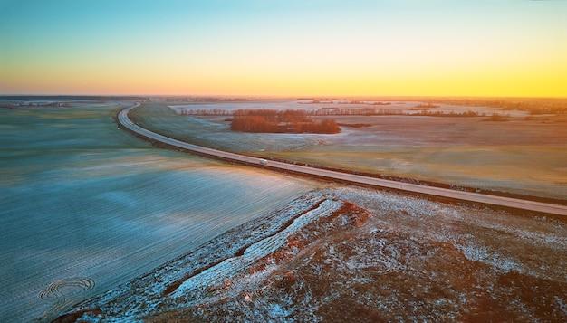 雪のパノラマの下で冬の緑の農地の冬の作物。高速道路12月の日没空中シーン。大きなアスファルト道路。田園地帯の上面図。ベラルーシ、ミンスク地方