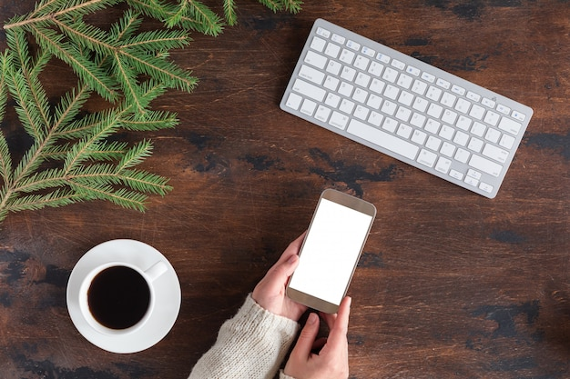 Winter green fir tree branches with cup of tea, mobile phone and white computer keyboard on wooden