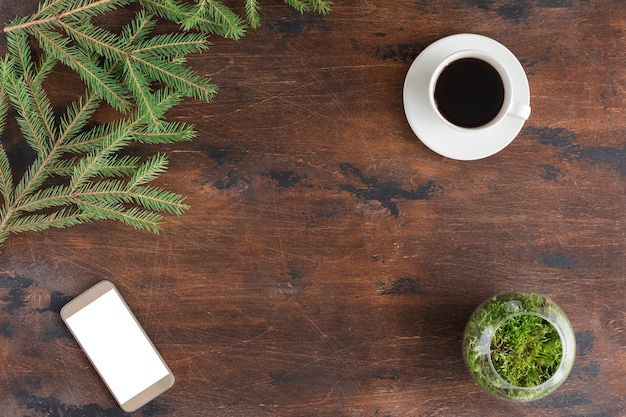 Winter green fir tree branches with cup of tea, mobile phone on wooden backgrond, flat lay and view from above