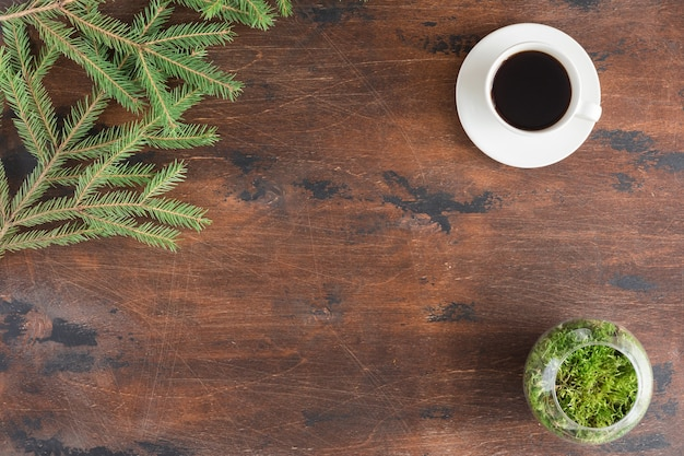 Winter green fir tree branches with cup of tea on wooden backgrond, flat lay and view from above