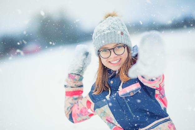 雪玉を投げて雪で遊ぶ冬の幸せな十代の少女。