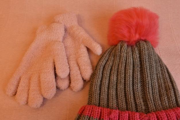 ピンクの背景に冬の帽子と手袋