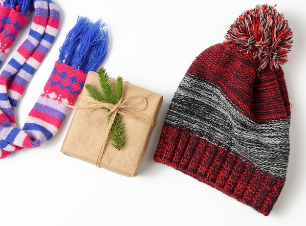 Winter hat,  gift box and multicolored knitted scarf on a white background, a set on a white background, top view