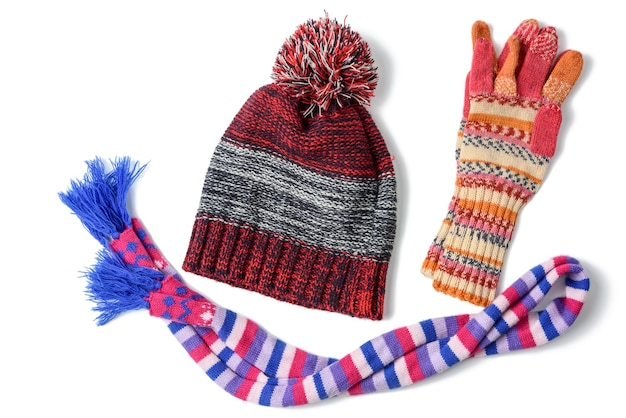 Winter hat, mittens and multicolored knitted scarf on a white background, a set on a white background, top view