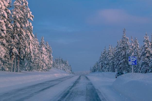 雪に覆われた森と駐車場の1台の車を通る冬の高速道路。フィンランドの夕べ