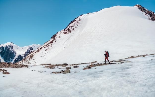 雪をかぶった山々での冬のハイキング。極端なレクリエーションと山岳観光。男性のハイカーが山道を下っていきます。背景には、雪をかぶった大きな山々。スペースをコピーします。