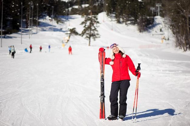 Зимний отдых и спортивная концепция с приключенческой женщиной с лыжами в руках у подножия горы.