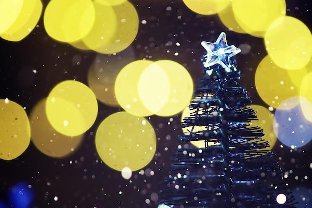 얼어붙은 전나무, 반짝이 조명, 보케가 있는 겨울 휴가 배경. 크리스마스와 새 해 휴일 배경 복사 공간.