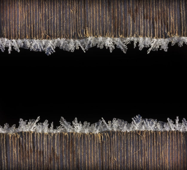 Winter holiday christmas new year background frame of macro photo frost on old wooden planks with black space for text