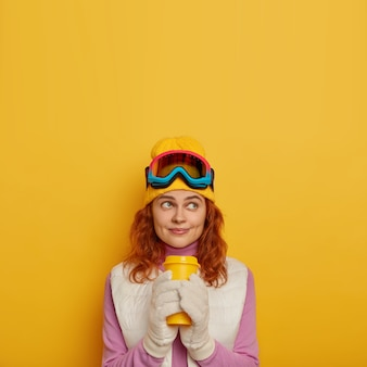 Концепция зимнего отдыха. привлекательная рыжая девушка имеет счастливое задумчивое выражение, держит кофе на вынос, пьет горячий напиток